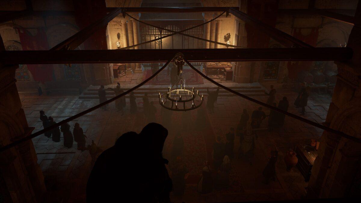 Eivor lauert in Assassin's Creed Valhalla über den Besuchern im Münster von Wincaester.