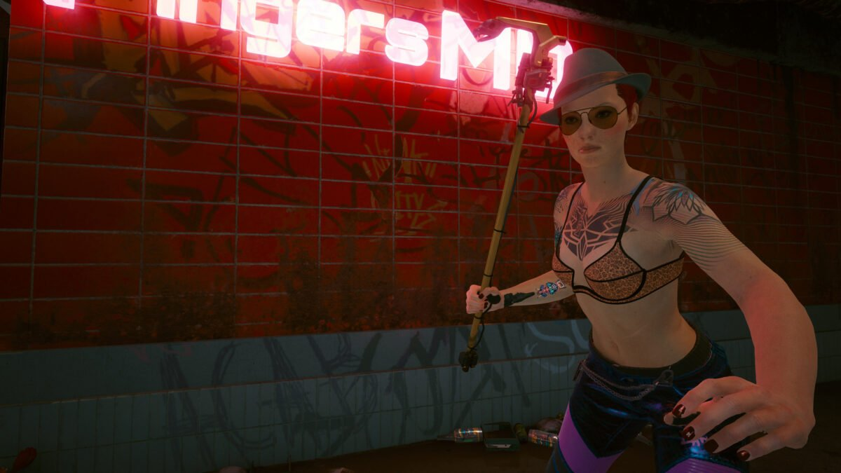 V with the iconic weapon Cottonmouth in front of Fingers' clinic in Cyberpunk 2077