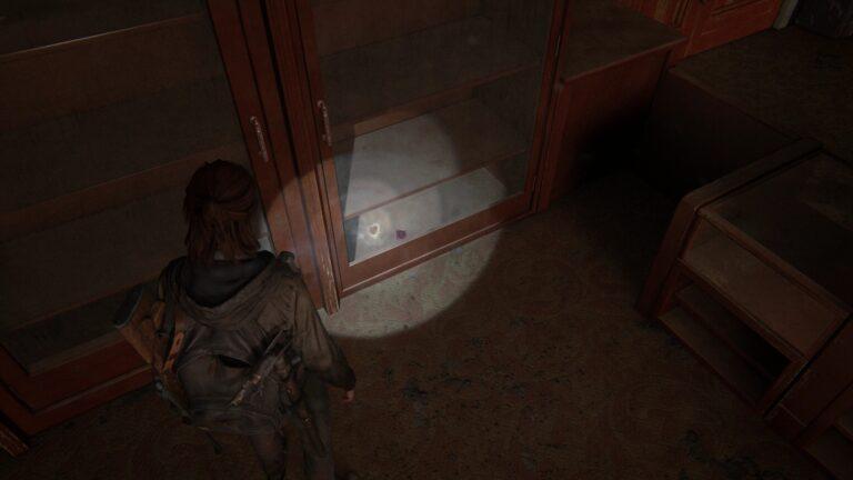 Sammelkarte am Boden eines Schrankes hinter Glas, im Foyer des Theaters in The Last of Us 2