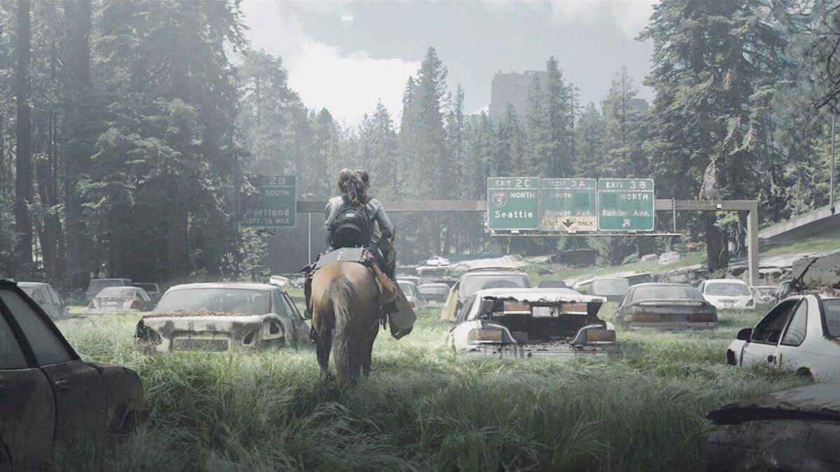 Ellie und Dina reiten auf einem Pferd zwischen Autowracks und hohem Gras auf einen Wegweiser in Richtung Seattle zu