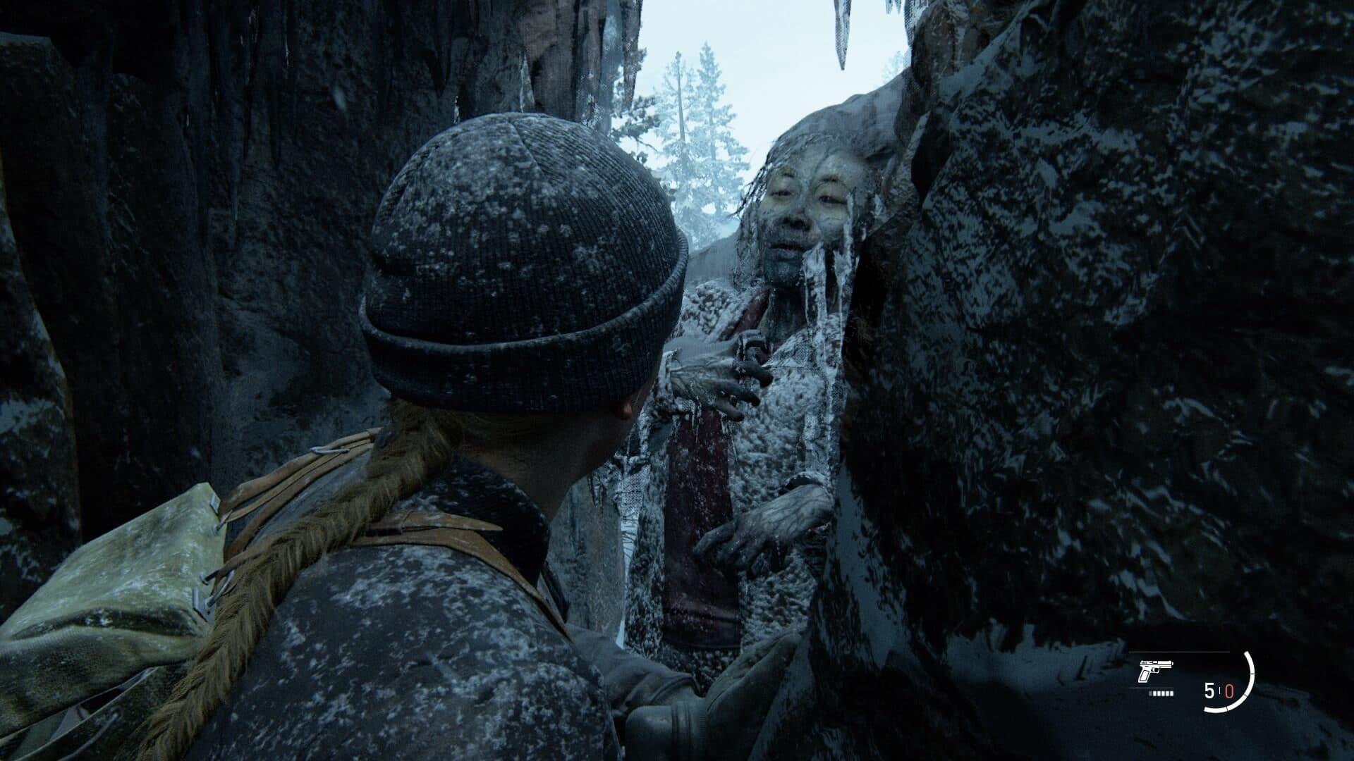 Eine Frau mit Mütze drückt sich durch eine Felsspalte, an deren Ende die gefrorene Leiche einer anderen Frau eingeklemmt ist.