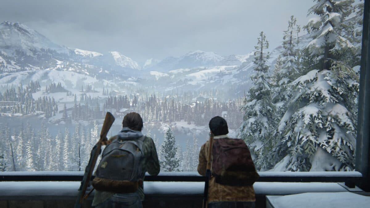 Zwei Frauen lehnen an einer Brüstung und genießen die Aussicht auf eine verschneite Gebirgslandschaft in dem Spiel The Last of Us Part II.