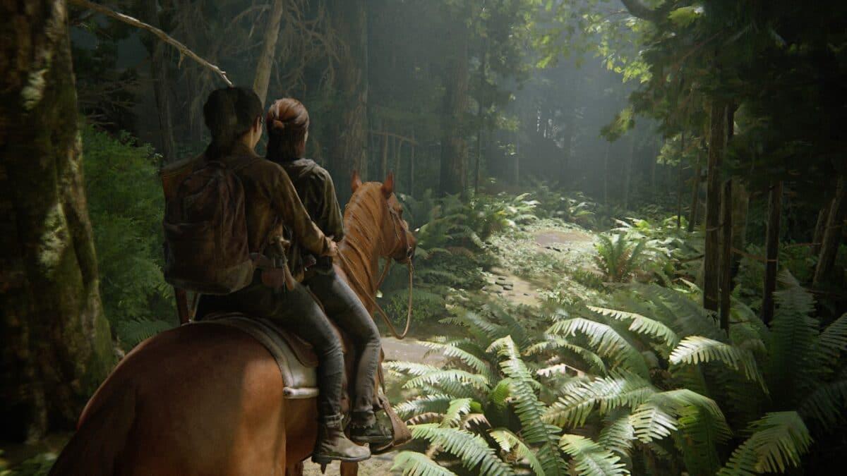 Ellie und Dina reiten auf einem Pferd durch einen Wald in The Last of Us 2.