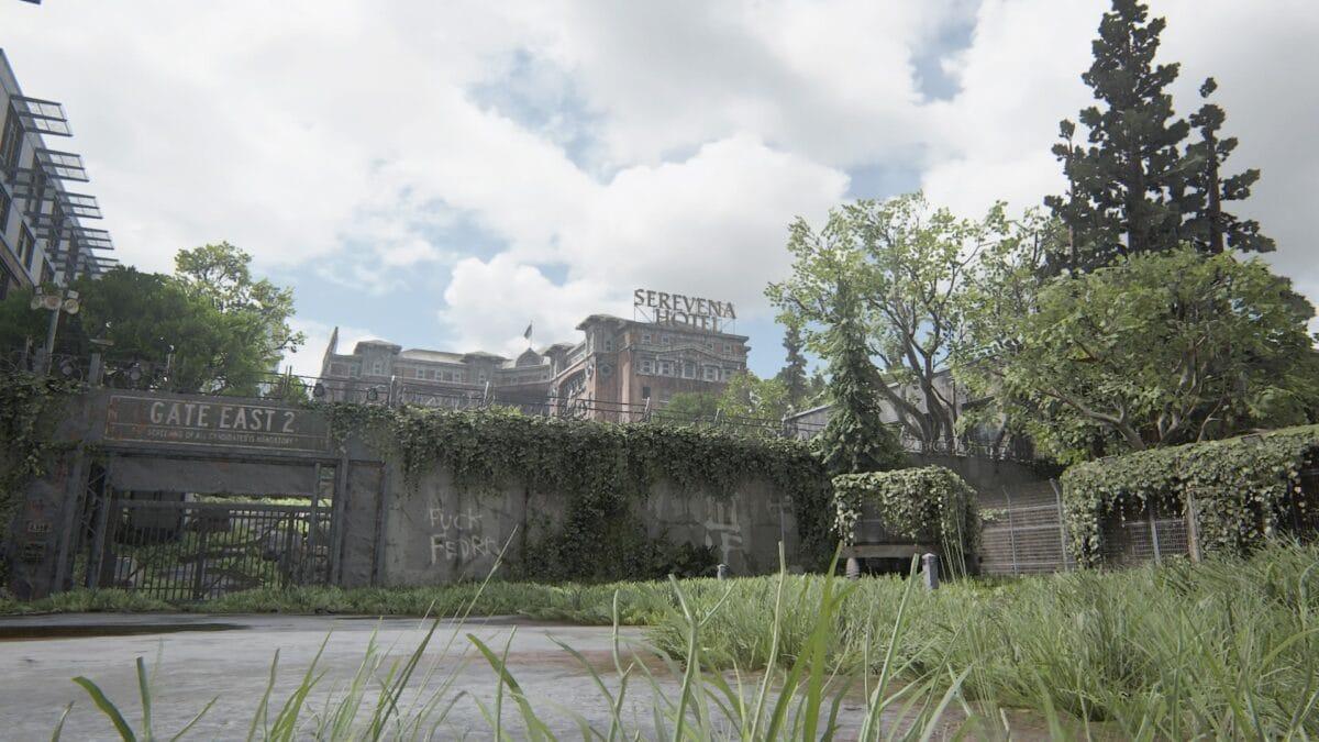 """Das Tor einer Absperrung mit der Aufschrift """"Fuck Fedra"""" verhindert den Zugang zum Serevena Hotel in The Last of Us Part 2."""