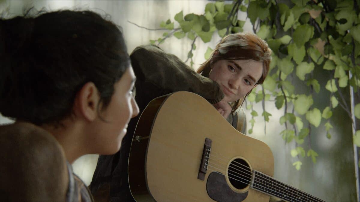Ellie hält eine Akustik-Gitarre auf dem Schoss und lächelt ihre Freundin Dina in The Last of Us Part 2 an.