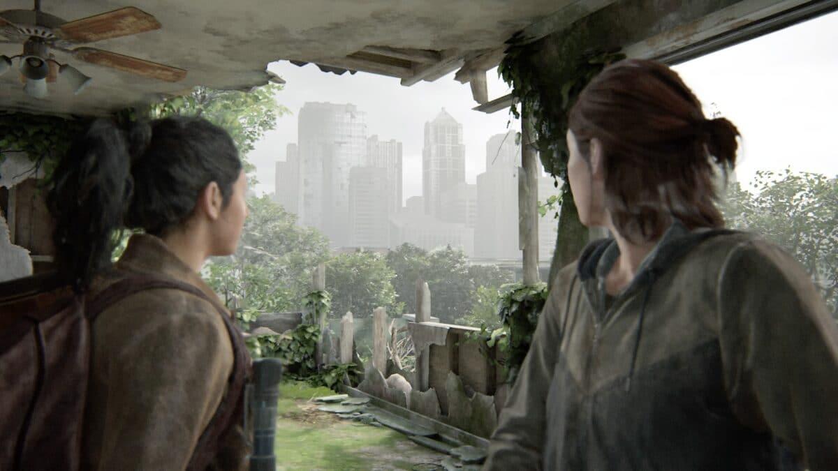 Dina und Ellie blicken durch eine zerstörte Wand auf ein paar Hochhäuser in der Ferne.