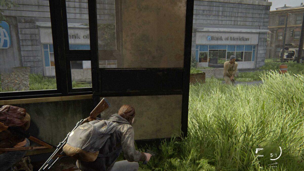 Ellie und Dina verstecken sich im Inneren eines leeren Geschäfts vor den WLF-Soldaten in The Last of Us Part 2.