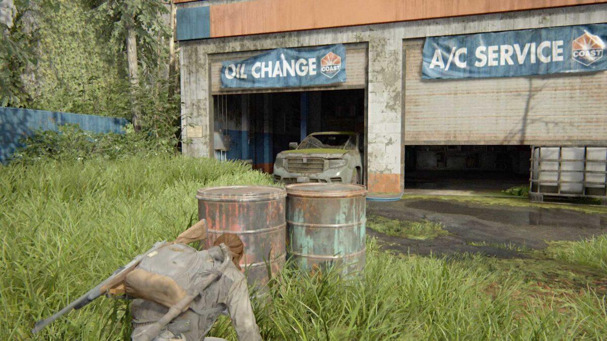 Ellie schleicht in der Deckung zweier rostiger Fässer auf eine Autowerkstatt in The Last of Us Part 2 zu.