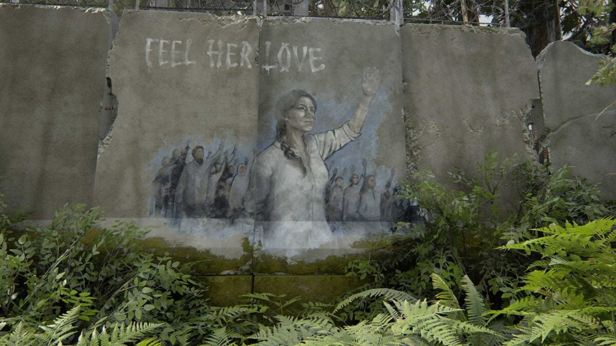 """Ein Graffiti an einer rissigen Wand in The Last of Us Part 2 zeigt eine Frau mit erhobenem Arm. Im Hintergrund sieht man viele Menschen mit der gleichen Geste. Darüber steht """"Feel her Love"""" in weißen Buchstaben."""