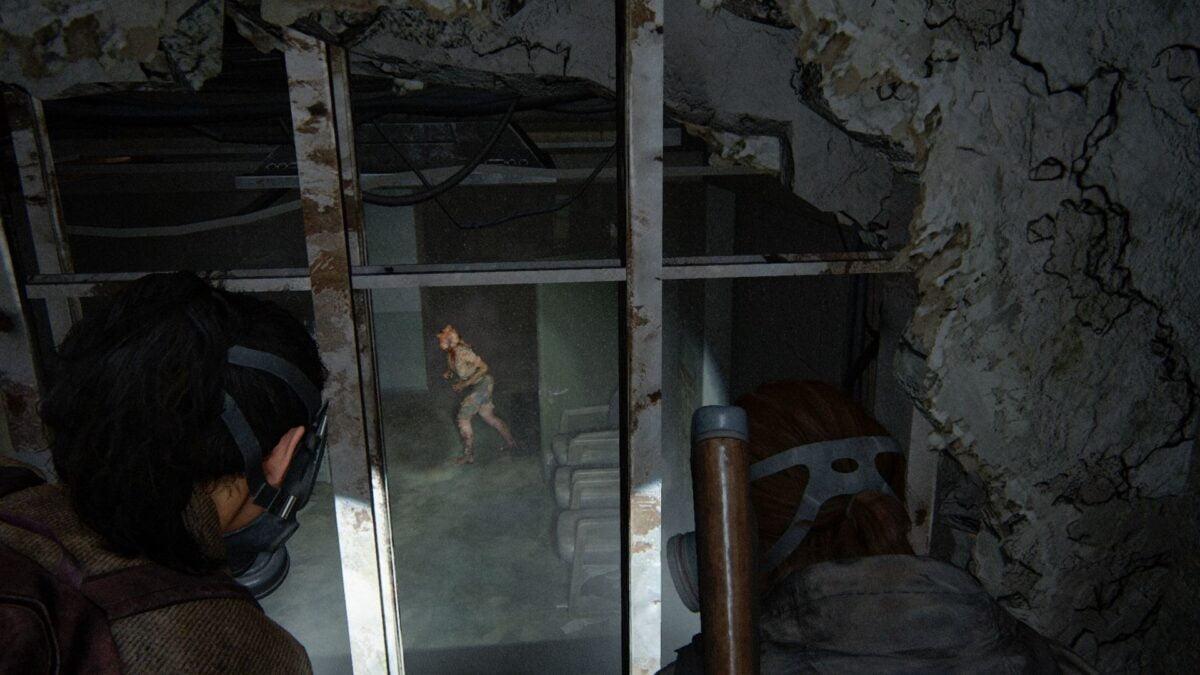Ellie und Dina beobachten in The Last of Us Part 2 einen Clicker, wie er im Raum unter ihnen umherstreift.