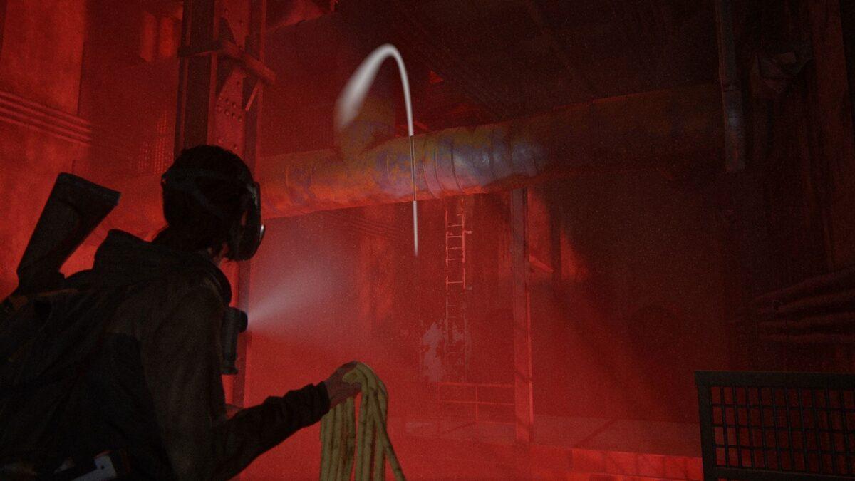 Ellie trägt eine Gasmaske und hält ein Seil in der Hand, das sie in The Last of Us Part 2 über ein Rohr werfen will.