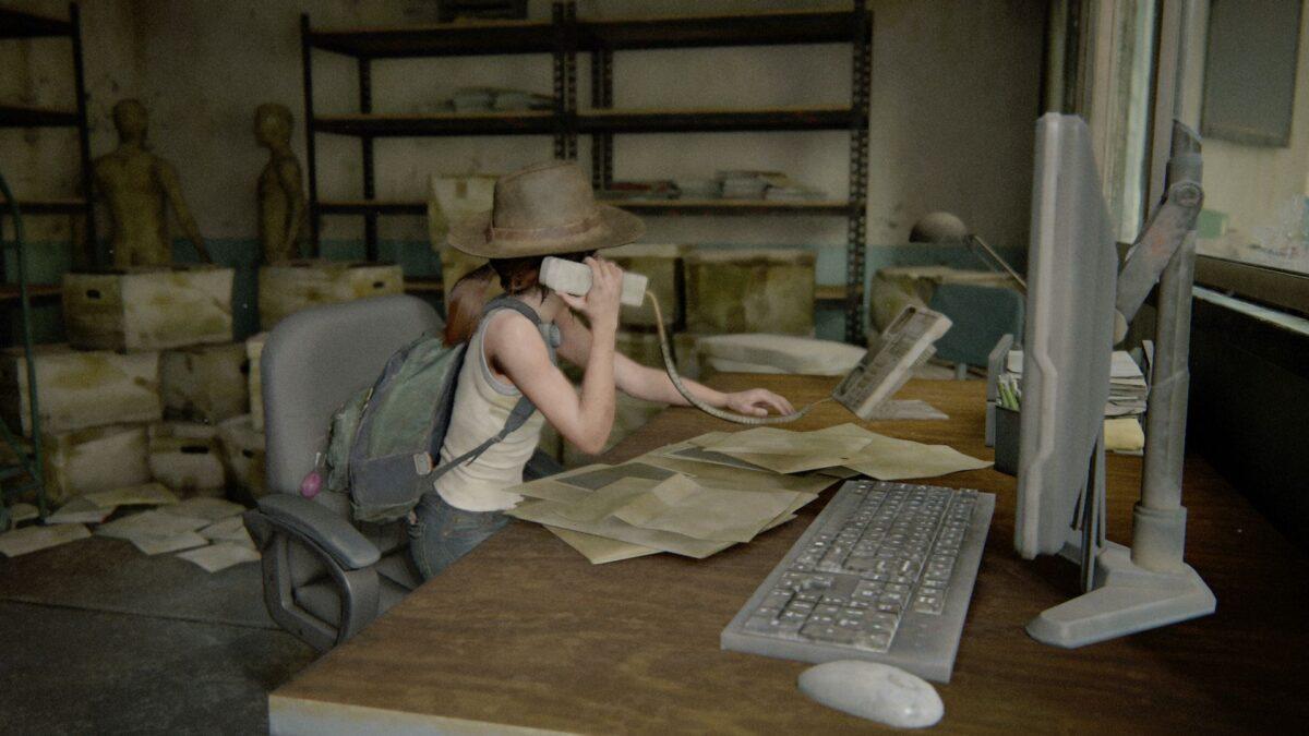 Ellie sitzt in The Last of Us Part 2 an einem Schreibtisch und spielt Sekretärin.