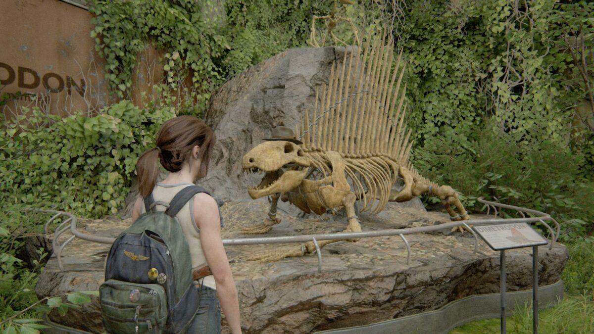 Ellie steht in The Last of Us Part 2 vor einem Dinosaurierskelett, dem sie einen Hut aufgesetzt hat.