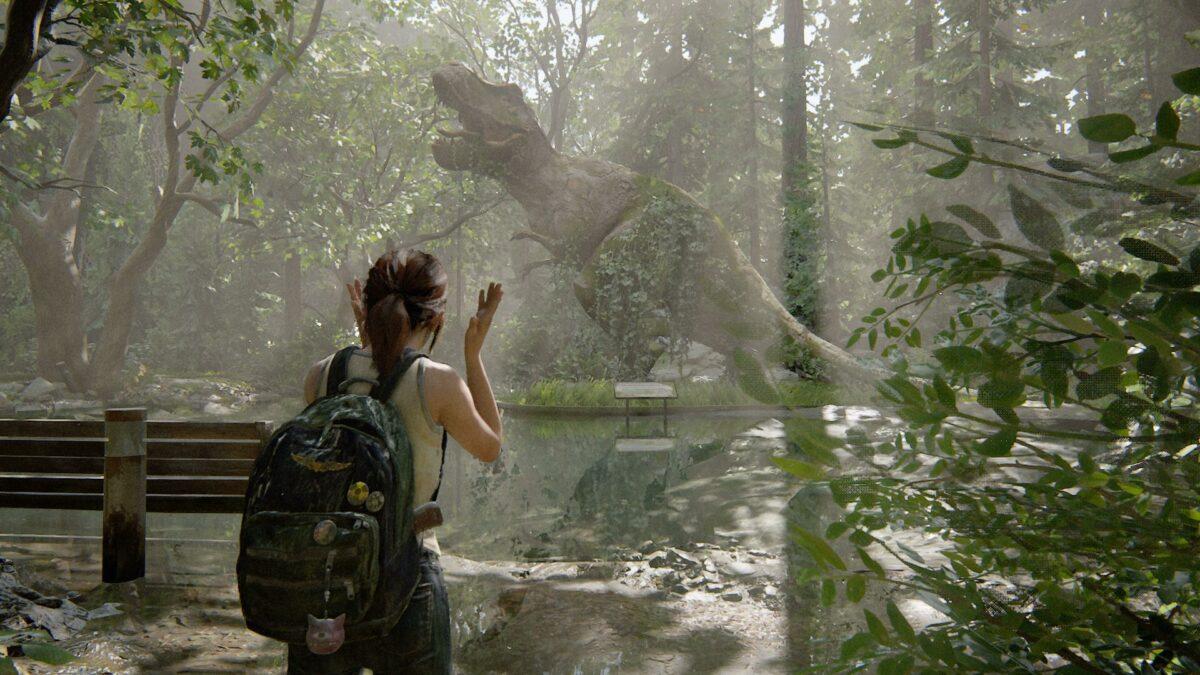 Die junge Ellie steht in The Last of Us Part 2 vor einer riesigen T-Rex-Statue.