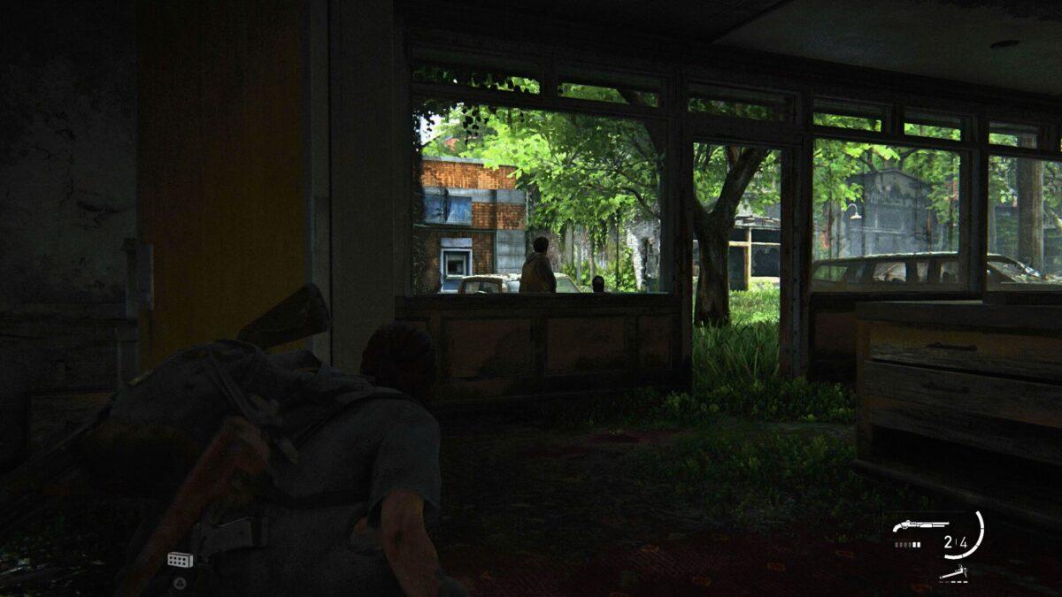 Ellie versteckt sich in einem der Läden von Hillcrest vor den WLFs in The Last of Us Part 2.