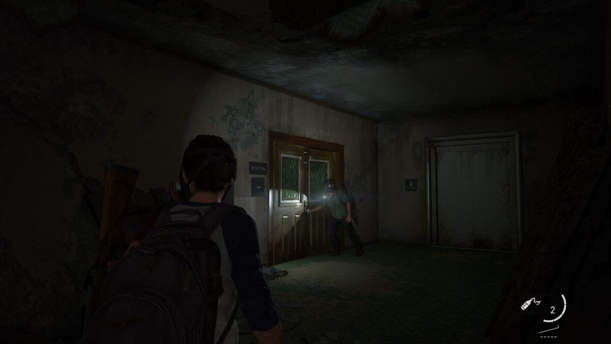 Ellie und Joel schleichen in The Last of Us Part 2 durch die sporenverseuchten Gänge eines Hotels.