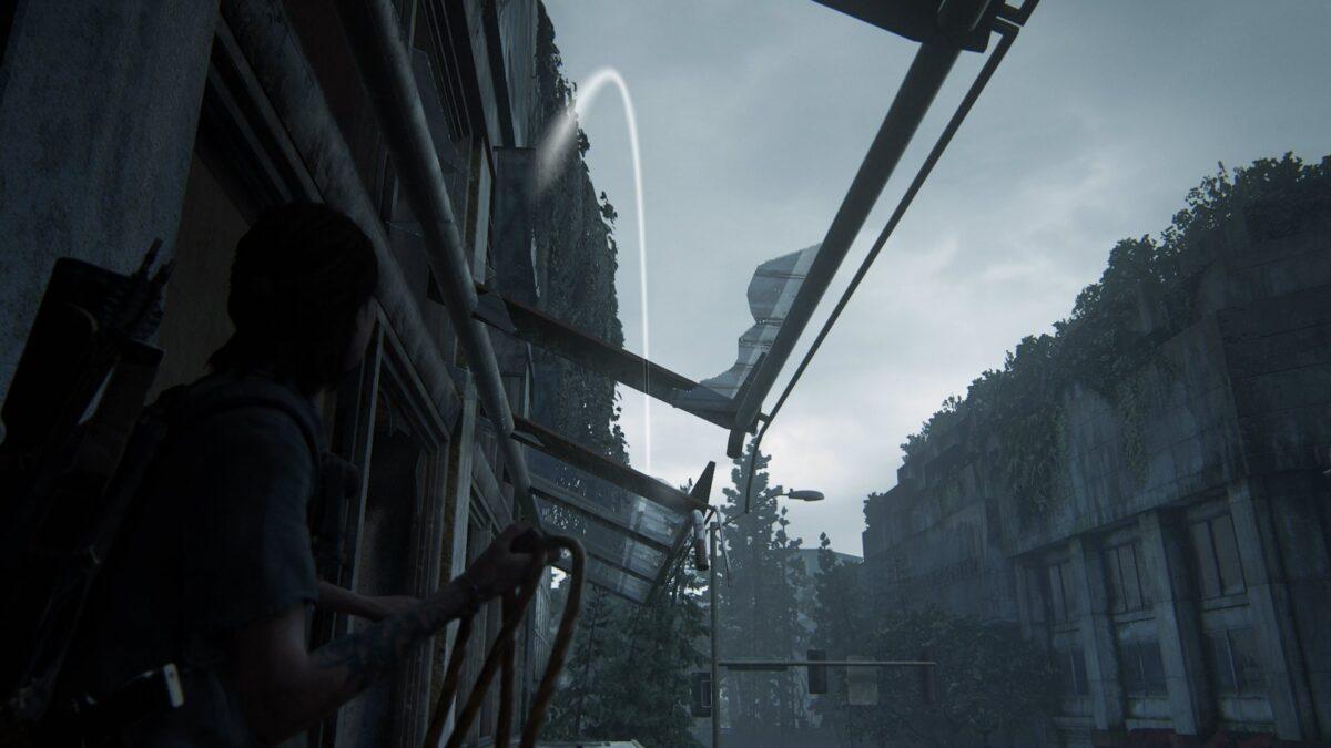 Ellie wirft ein Kabel durch ein zerbrochenes Fenster in The Last of Us Part 2.