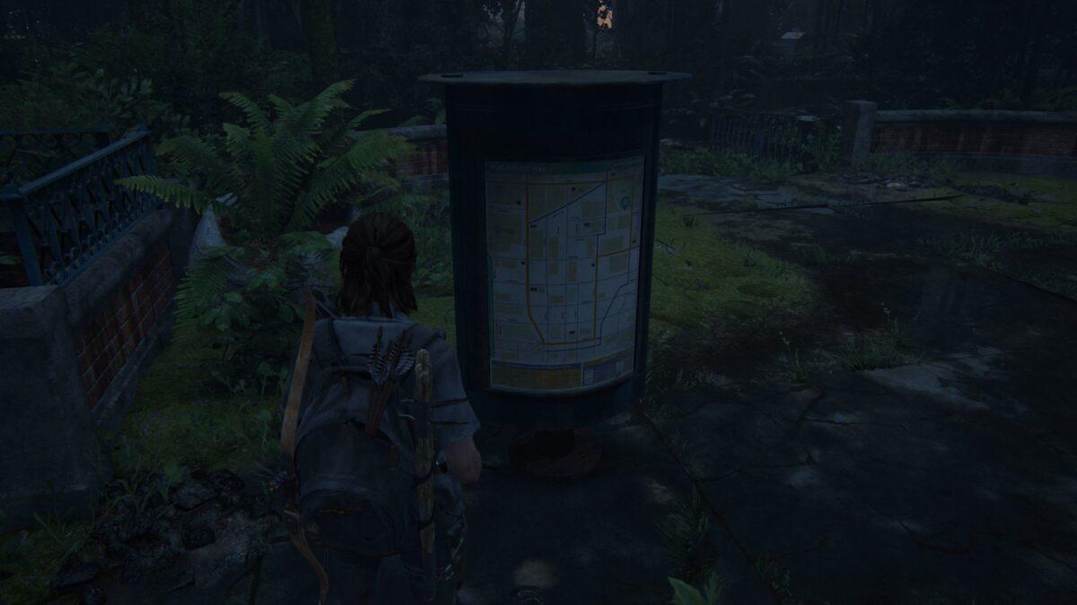 Ellie sieht sich eine Karte des vor ihr liegenden Gebiets in The Last of Us Part 2 an.