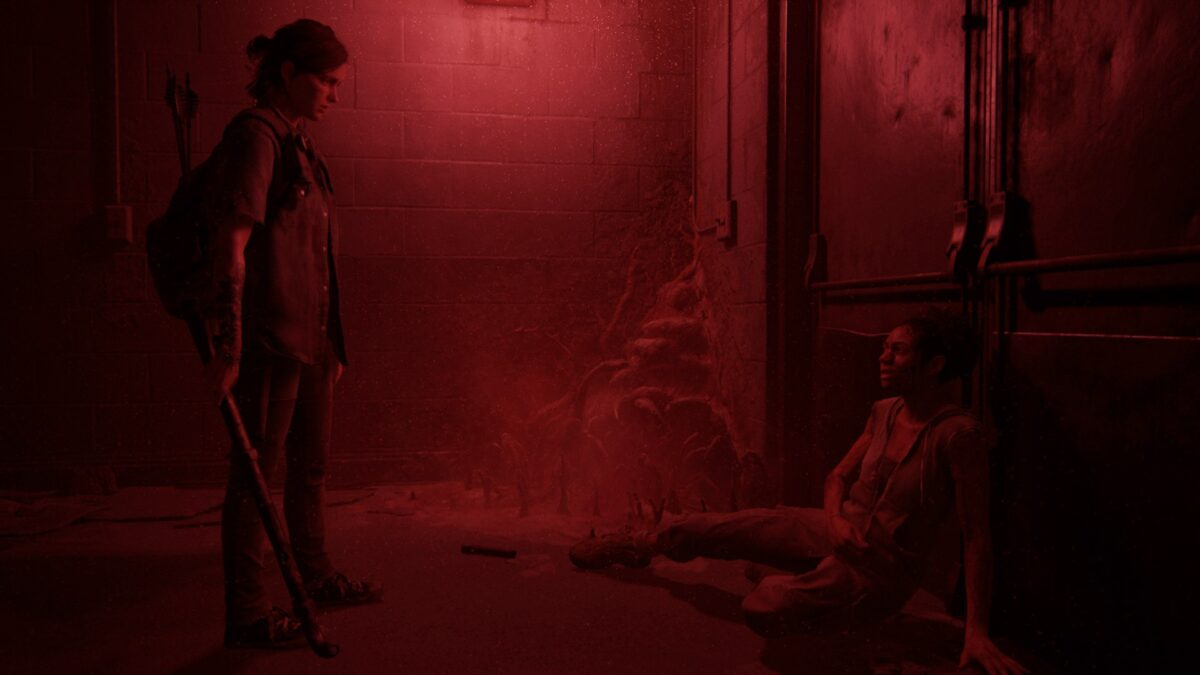 Ellie und Nora stehen sich im roten Schein des Kellerlichts in The Last of Us Part 2 gegenüber.