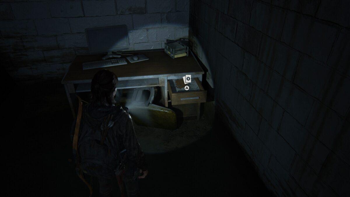 Ellie steht in The Last of Us 2 vor einem Schreibtisch, in dessen Schublade eine Sammelkarte liegt.