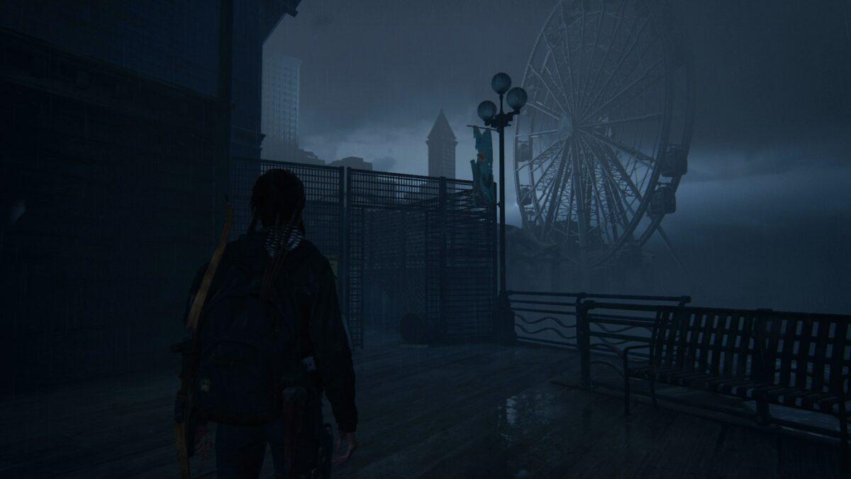Ellie steht in The Last of Us 2 vor einem kaputten Zaun mit Blickrichtung auf ein Riesenrad.