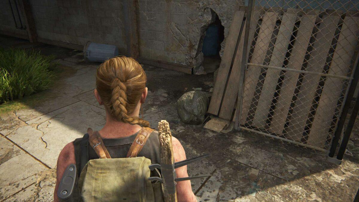 Abby steht in The Last of Us 2 vor einem Loch in einer Gebäudewand.