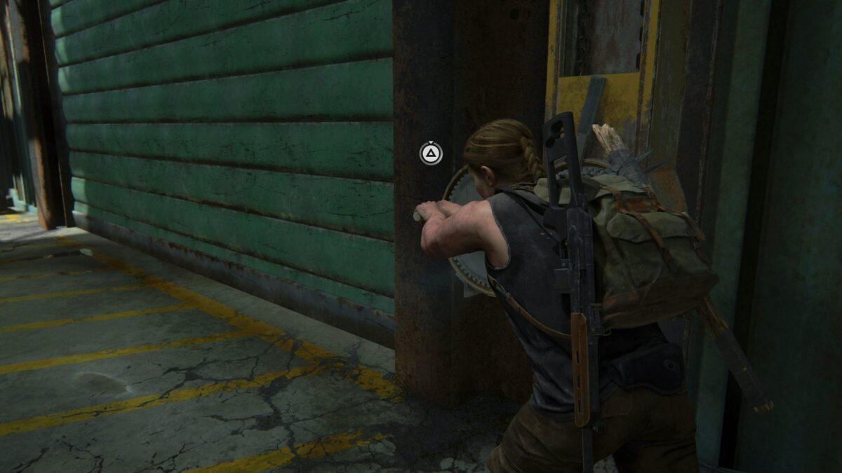 Abby versucht in der Bootswerkstatt von The Last of Us 2 ein Tor aufzukurbeln.