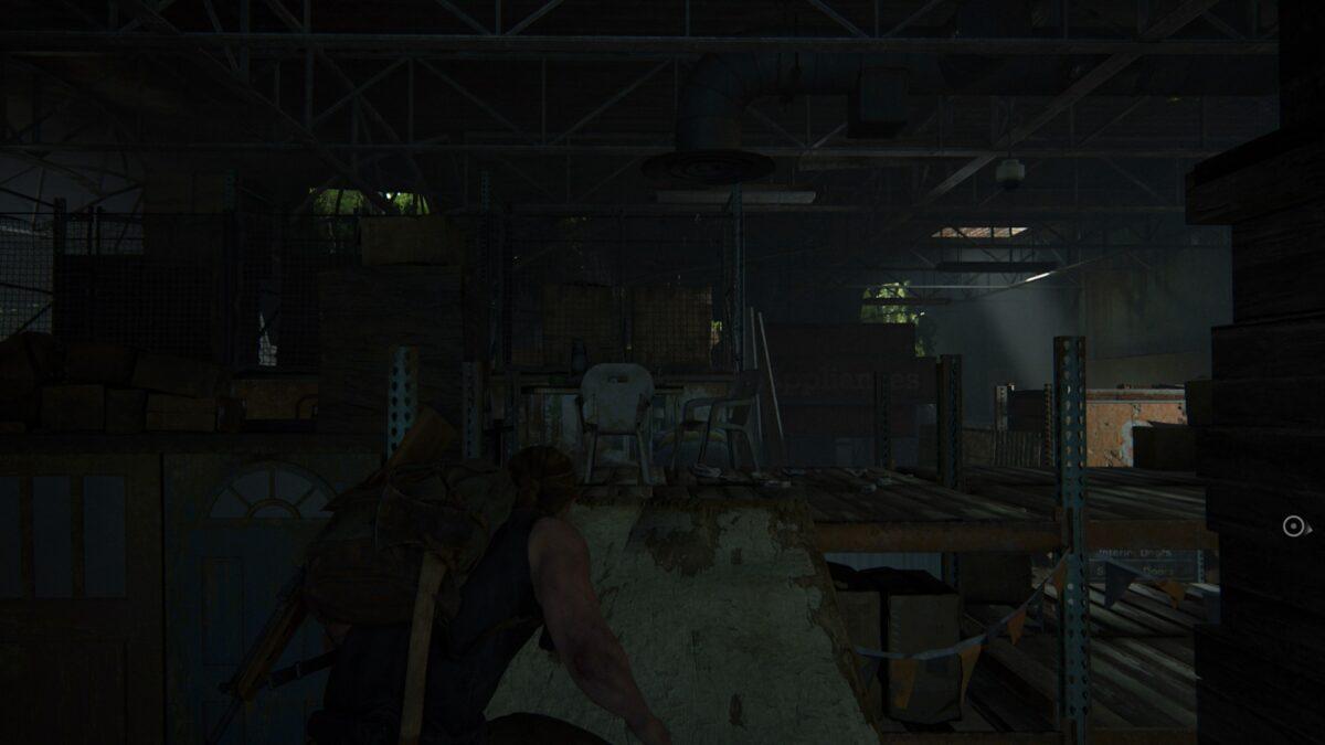 Abby klettert in The Last of Us 2 über eine Planke zwischen den Lagerregalen umher.