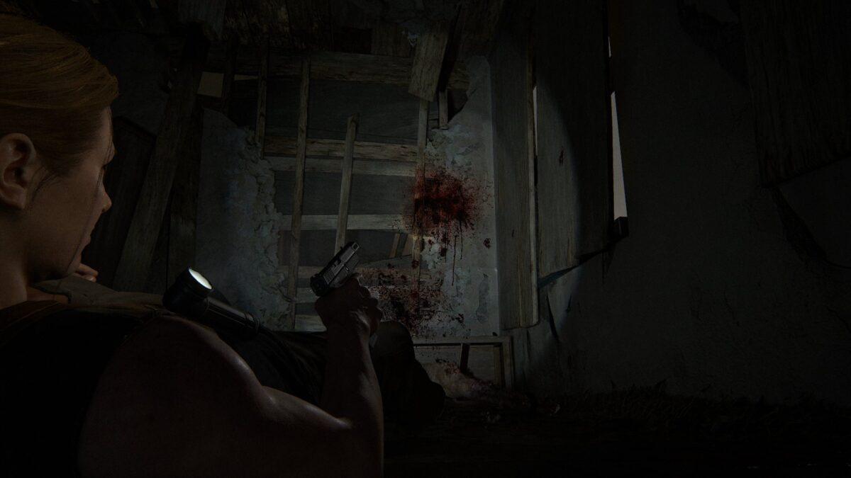 Abby liegt in The Last of Us 2 mit gezückter Waffe am Boden und blickt auf einen Blutspritzer.