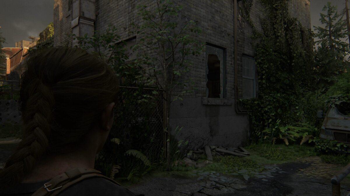 Abby steht in The Last of Us 2 vor einem zerbrochenen Fenster.