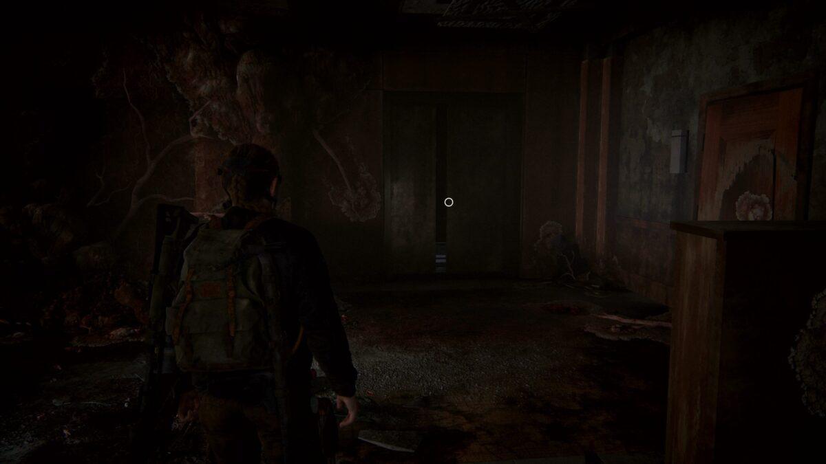 Abby steht in The Last of Us 2 im Hotel-Flur vor einem Aufzug.