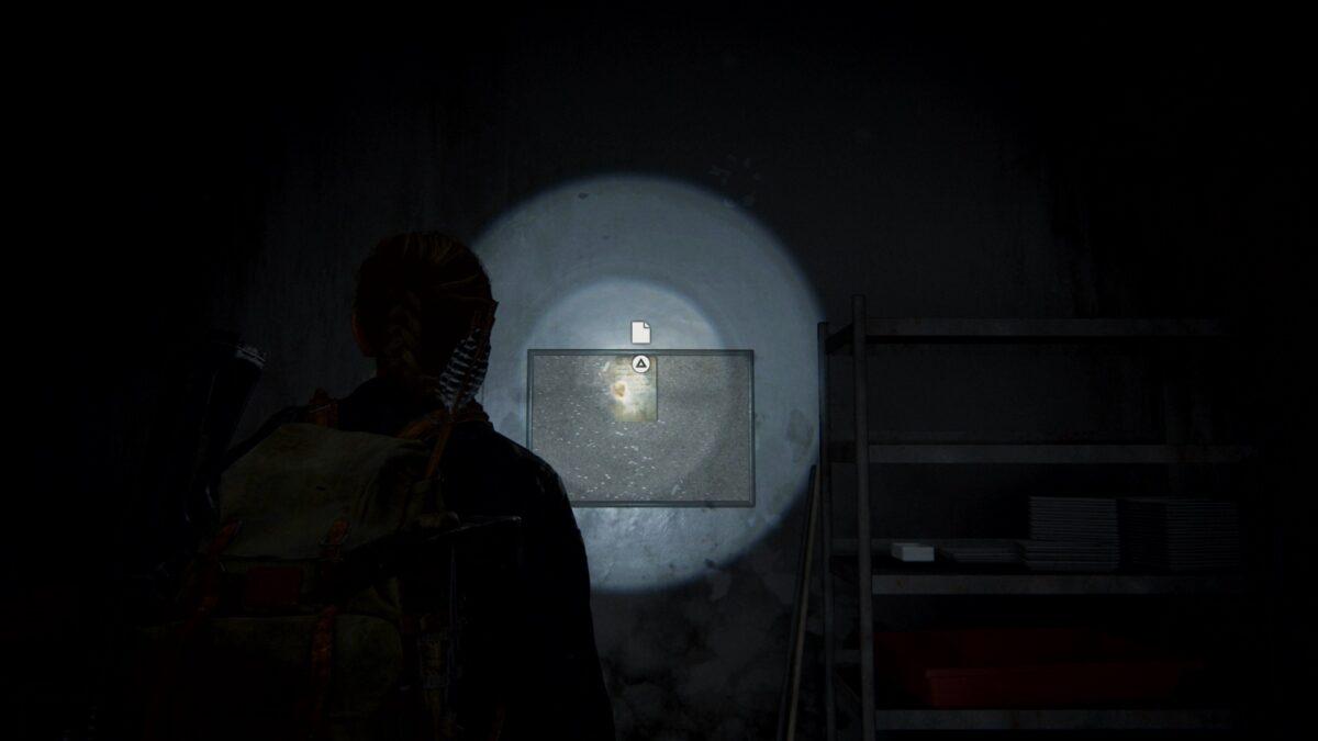"Abby steht in The Last of Us 2 vor dem Artefakt ""Safekombination Fitnessstuido""."