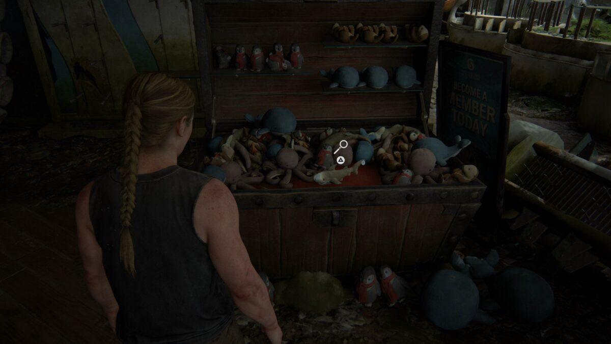 Abby steht in The Last of Us 2 vor einer Truhe mit Plüschfiguren.