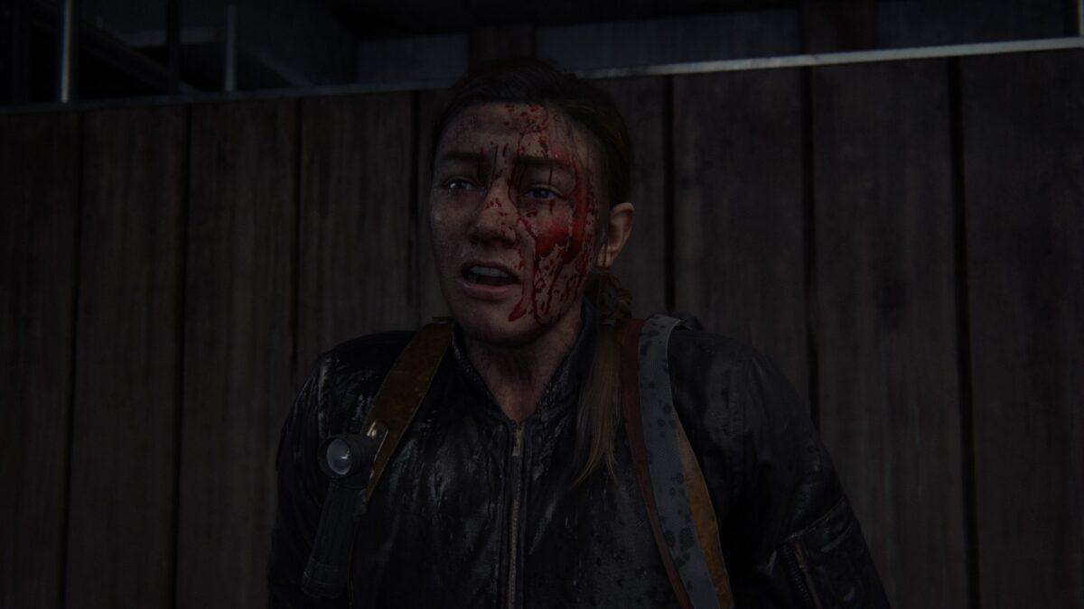 Abby sitzt in The Last of Us 2 mit blutverschmiertem Gesicht am Boden.