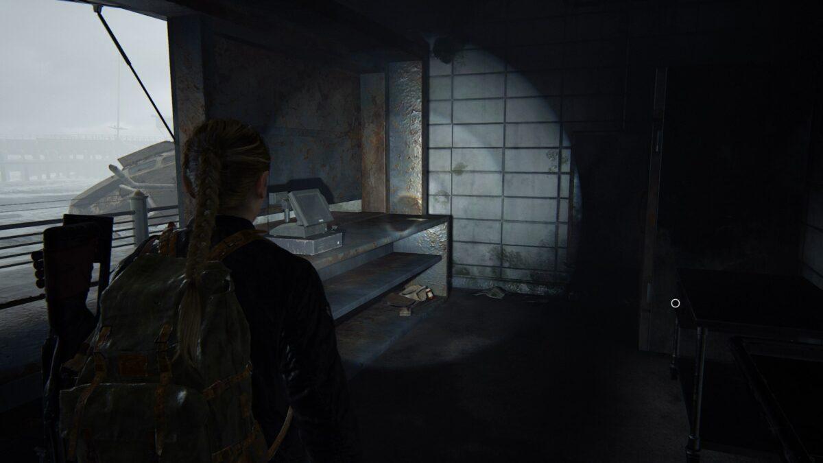 """Abby steht in The Last of Us 2 in einem Imbiss vor dem Artefakt """"Jachthafen-Notiz""""."""