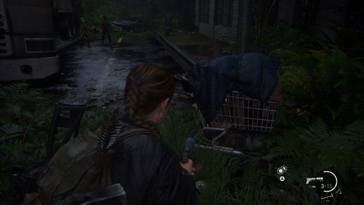 """Abby steht in The Last of Us 2 vor einem Einkaufswagen, in dem die Münze """"Arkansas"""" liegt."""