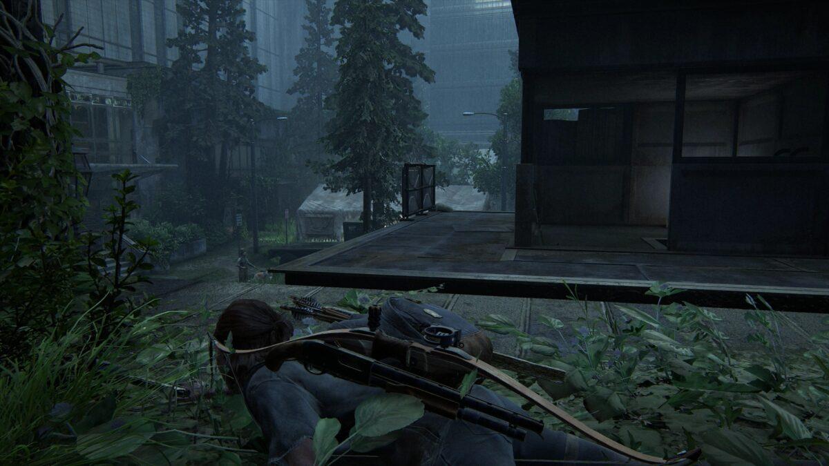 Ellie liegt auf einer Plattform im ersten Stock auf dem bauch während unten im Krankenhaushof eine WLF-Patrouille herumläuft