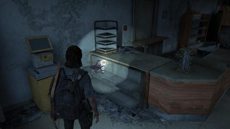 Die Sammelkarte Bhat M'Andarr liegt neben einem Sammelkarten-Display vor einem Tresen in The Last of Us 2