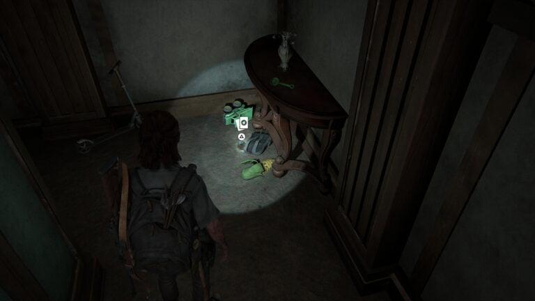 Die Sammelkarte Doppelganger neben einem Rucksack und zwischen Spielsachen auf dem Flur in The Last of Us 2