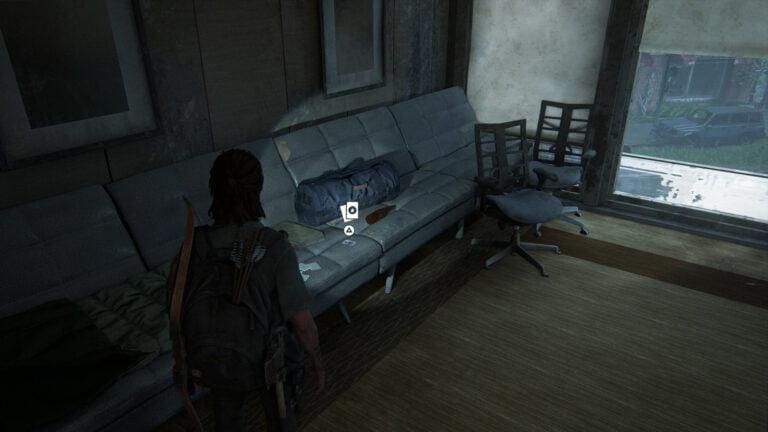 Die Sammelkarte Shift auf der Couch neben einer WLF-Tasche in The Last of Us 2