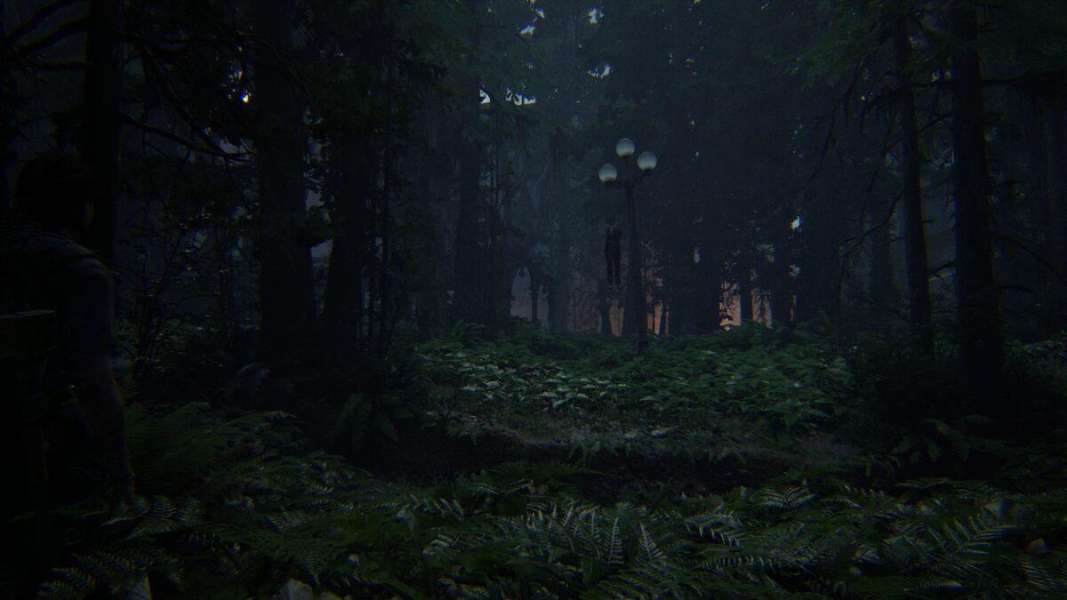 Blick auf den zugewucherten Pilgrim Park mit einer an einem Baum hängenden Leiche in The Last of Us 2