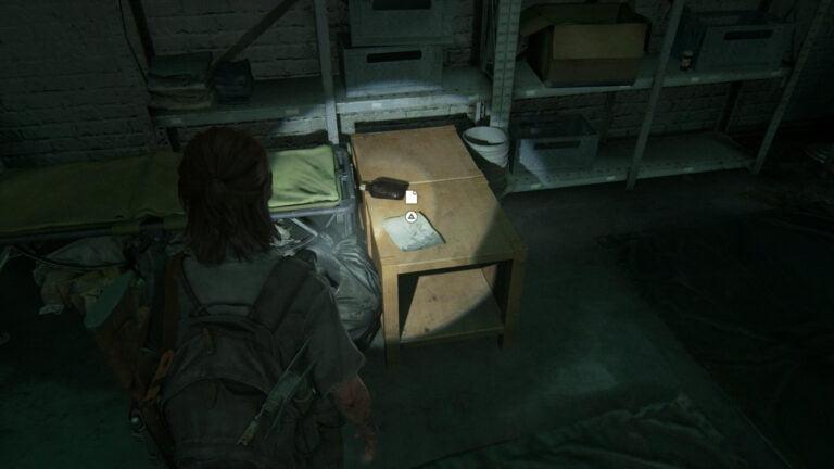 """Das Artefakt """"Zeichnung von Boris Tochter"""" auf einem Tischchen neben einer Liege in The Last of Us 2"""