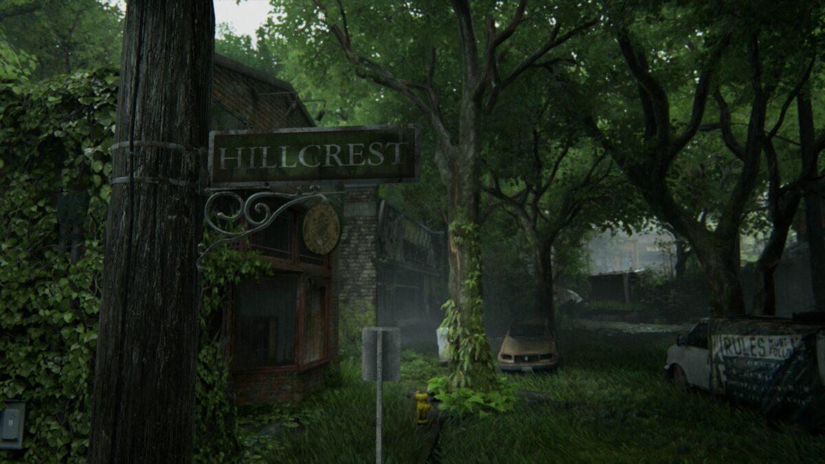 Straßenschild Hillcrest mit Blick auf eine überwucherte Allee und alte Autowracks, am Straßenrand Häuserruinen in The Last of Us 2