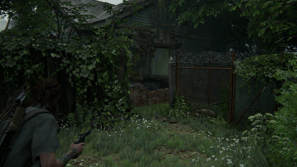 Ellie sieht auf einen Mauerdurchbruch einer Ruine in The Last of Us 2.
