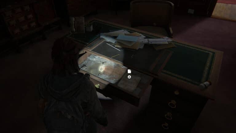 Schreibtisch mit offener Schublade und darin das Artefakt Brief von Rabbi Saunders in The Last of Us 2