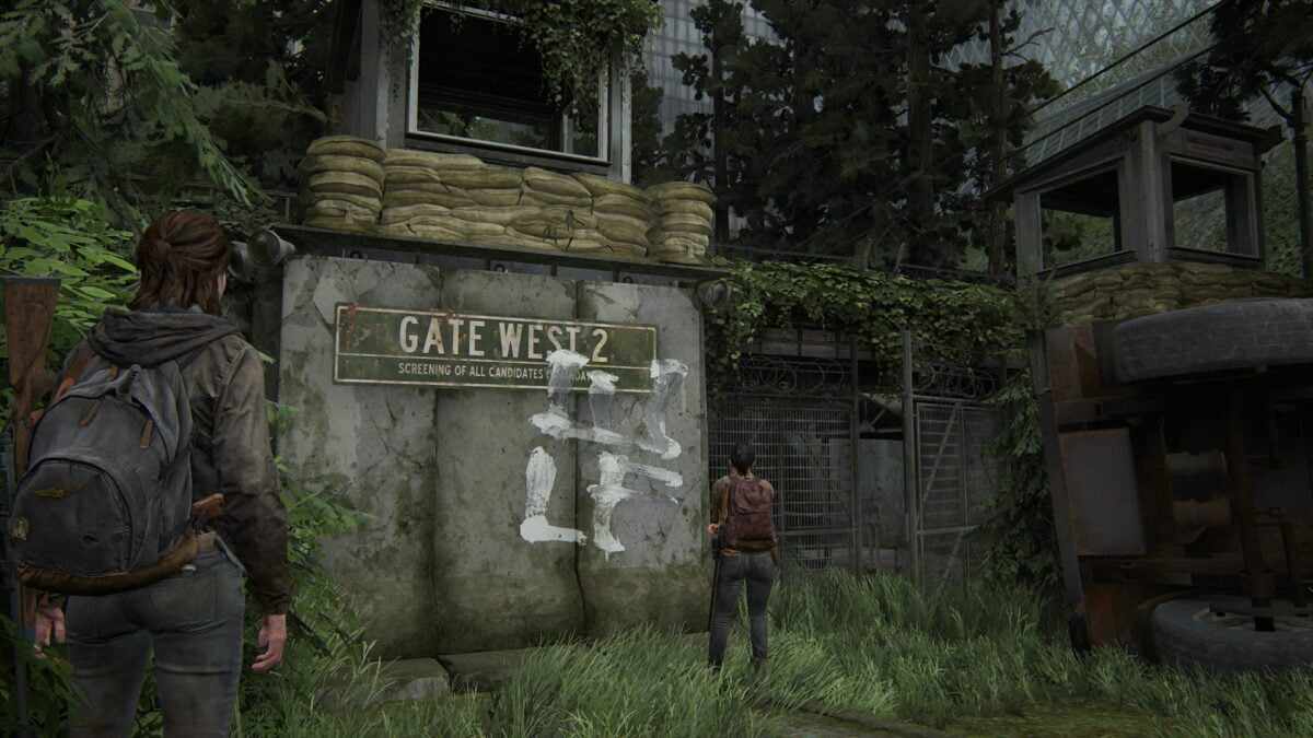 Ellie and Dina in front of the WLF graffiti-smeared Gate West 2 in The Last of Us 2.
