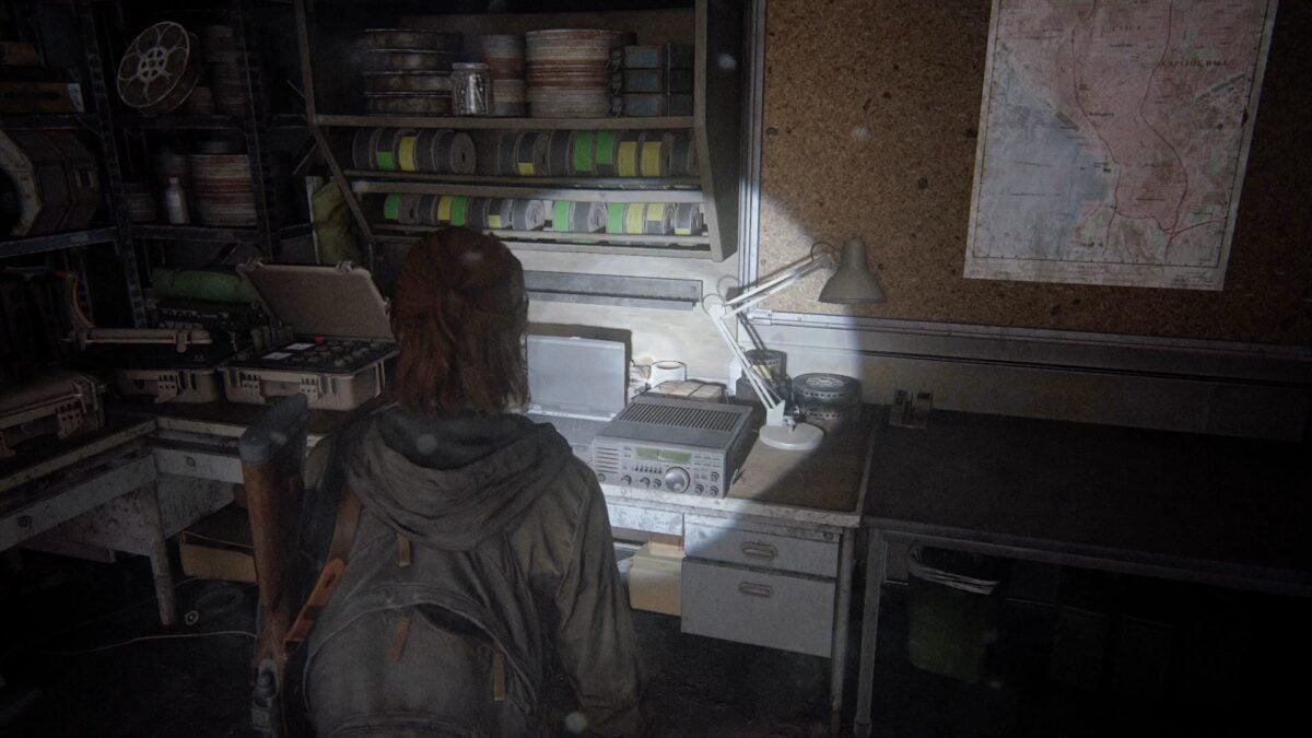 Ellie steht in The Last of Us Part 2 vor einem alten Funkgerät, das auf einem Tisch steht.