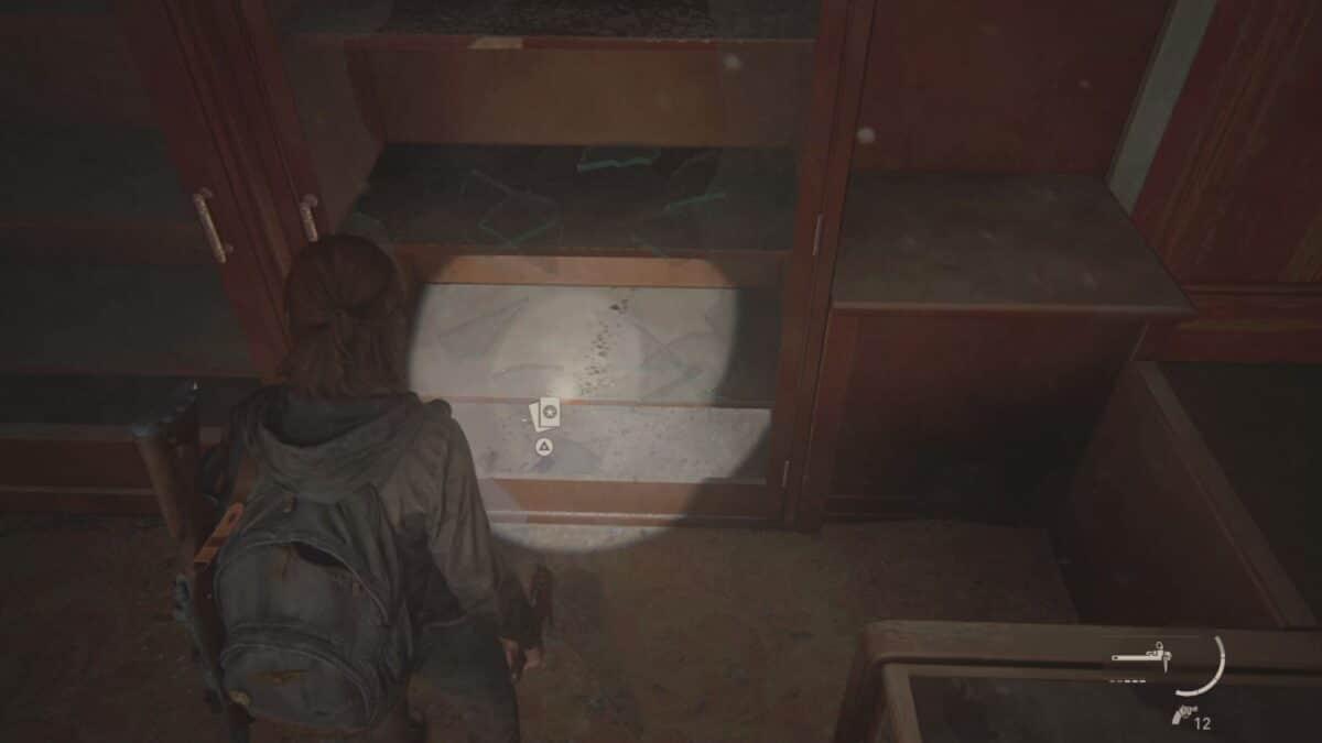 Ellie steht in The Last of Us Part 2 vor einem Schrank, dessen Glastür sie zerbrochen hat, um eine Sammelkarte aufzuheben.