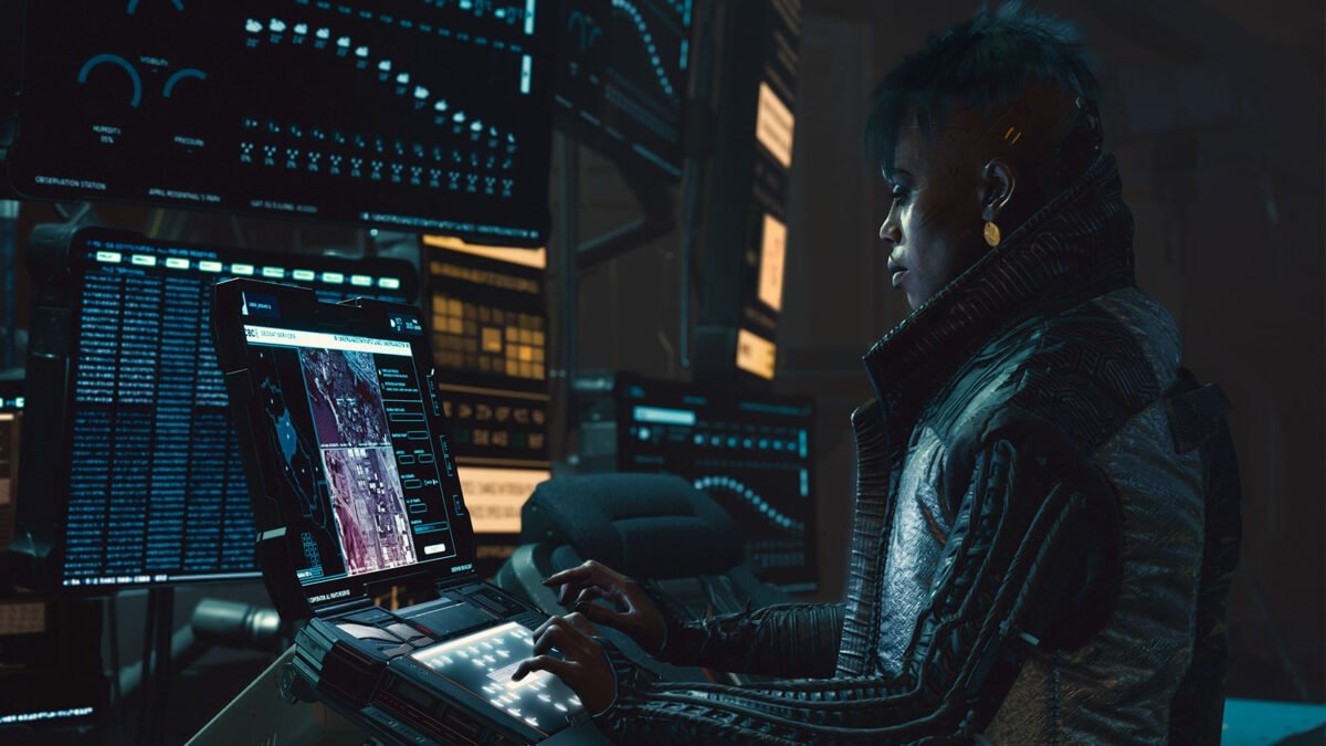 Cyberpunk 2077 Netrunner of Vodoo Boys stands in front of several screens and hacks into a system