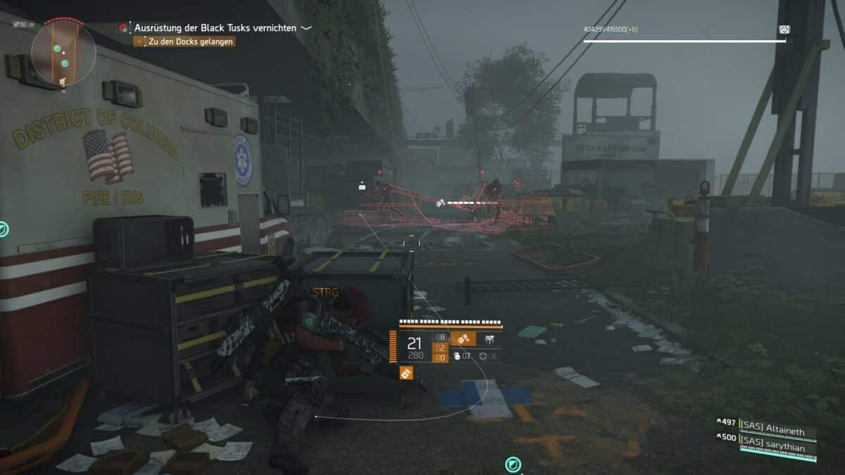 Eine Division-Agentin kauert im Vordergrund hinter Kisten, während anstürmende Gegner im Hintergrund von einer ihrer Fähigkeiten erfasst werden.